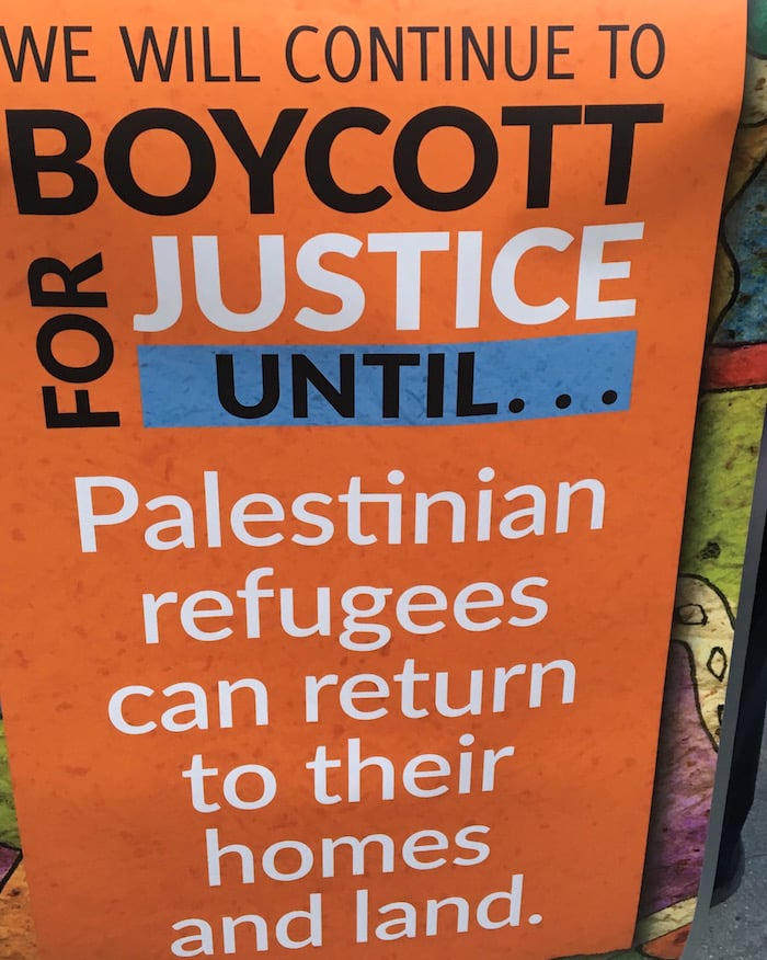 Sign reads: we will continue to boycott for justice until Palestinian refugees can return to their homes and land.